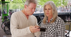 Couple of elderly Caucasian people reading directions on smartphone device Stock Footage