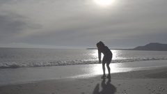A young woman exercising and doing a burpee on the beach. Stock Footage