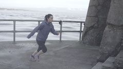 A young woman running on a breakwall, super slow motion. Stock Footage