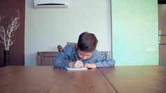 Little boy doing homework at home Stock Footage