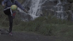 A young woman juggles a soccer football in front of a waterfall, super slow moti Stock Footage