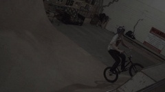 A boy rides a BMX bike on an indoor skate park half pipe ramp, super slow motion Stock Footage