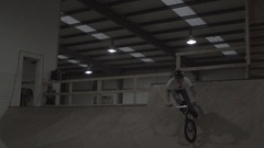A boy rides a BMX bike on an indoor skate park half pipe ramp. Stock Footage