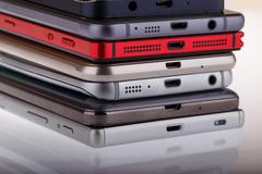Pile of mobile phone. Heap of the different smartphones on white background. Stock Photos