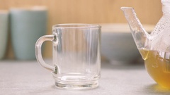 Serving hot tea from glass teapot in teacup. Stock Footage