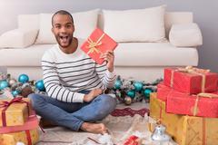 Happy optimistic man holding his present Stock Photos