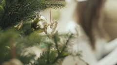 Pretty girl in christmas cap using smartphone behind christmas tree Stock Footage