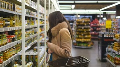 Young woman coming up to shelves in shop and taking product from it Stock Footage