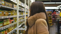 Beautiful girl select delicious canned olives at store and putting it Stock Footage