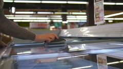 Young woman taking product from fridge in shop. Close up Stock Footage