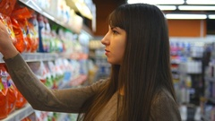 Young woman choosing household chemicals in supermarket. Selects fabric softener Stock Footage