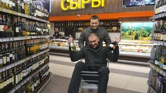 Young happy man with alcohol bottles at hands riding inside shopping cart Stock Footage