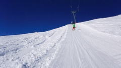 POV of riding on a T-bar lift while skiing in the mountains in fresh powder snow Stock Footage