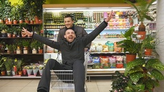 Happy smiling guy sitting in supermarket trolley and going through store Stock Footage