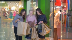 Excited, happy shopaholics, girls, friends shows each other shopping bags in a Stock Footage