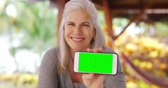 Happy mid aged woman smiling at camera while holding phone Stock Footage