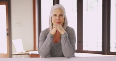 Beautiful mid aged Caucasian woman sitting and smiling Stock Footage