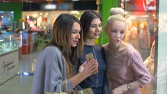 Happy young girls excitedly looking at shop window, showcase. Consumerism and Stock Footage