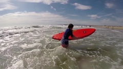 An 8-year-old boy learns to surf at the beach, slow motion. Stock Footage