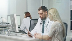 In Doctor's Office Professional Doctor Consults Beautiful Young Woman with a Hel Stock Footage