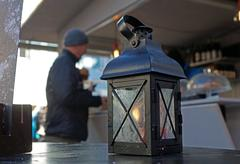 Lantern with candle and light, sundown in the mountains on the background Stock Photos