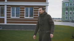 A man in a gray coat in the autumn weather walks on a footpath. Against the Stock Footage