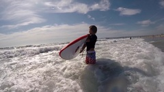 An 8-year-old boy learns to surf at the beach. Stock Footage