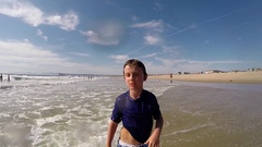 An 8-year-old boy makes a funny face expression and gesture at the beach, slow m Stock Footage
