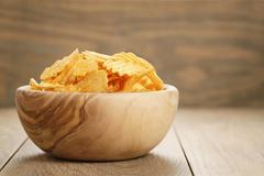 Rippled potato chips with paprika flavour in wooden bowl Stock Photos