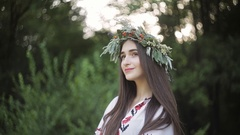 A young girl of Slavic appearance with a wreath of wild flowers on the MidSummer Stock Footage