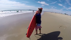 A boy carries his surfboard to the waves at the beach, slow motion. Stock Footage