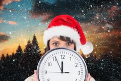 Woman in santa hat holding a wall clock against digitally generated background Stock Photos