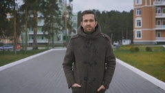 Happy dark-haired man with beard in brown coat walking along the street with Stock Footage