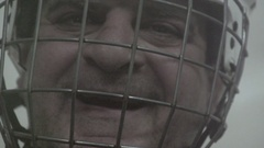 Portrait of an ice hockey player wearing a helmet with a face mask, super slow m Stock Footage