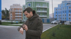Courtyard houses. A man in a gray coat with a clock on hand and with a ring on Stock Footage