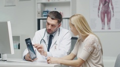 Doctor Shows to His Woman Patient Tablet Computer with X-Ray on it. Arkistovideo