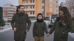 Happy young family in warm clothing are walking together on the street laughing Stock Footage