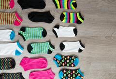 Colorful socks on grey wooden background. Top view. Copy space. Stock Photos