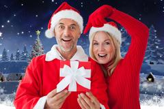 Couple in santa costume showing their gift against digitally generated christmas Stock Photos