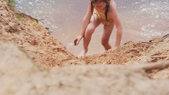 Smiling cute little girl in a swim suit crawling on a beach and jumping into Stock Footage