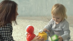 Mother plays with little baby girl with blocks and doll on carpet Stock Footage