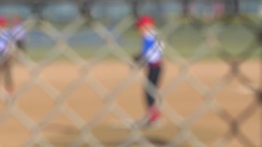 Detail of a chain-link fence at a little league baseball game, slow motion. Stock Footage