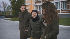 Family walking on a footpath. The man in the gray coat listens to his wife Stock Footage