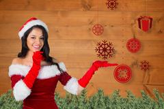 Smiling woman in santa costume pretending to catch snowflake Stock Photos