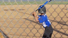 A batter is at bat while playing in a boys little league baseball game, slow mot Stock Footage