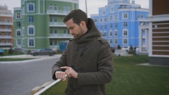 A man in a gray coat with a clock on hand and a ring on his finger is in the Stock Footage