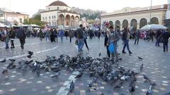 4K Bird feeding Monastiraki Metro square Tsisdarakis Mosque and Acropolis Athens Stock Footage