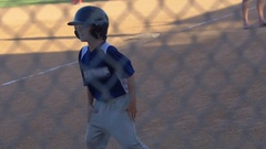 Boys celebrate a home run at a little league baseball game, slow motion. Stock Footage