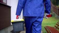 Handyman services - worker with tool box going to client house Stock Footage