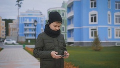 Child in warm dark grey jacket and black cap and scarf playing phone standing in Stock Footage
